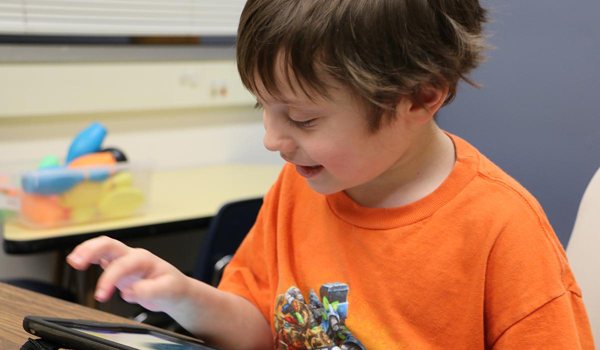 Luke Holzem works with his communication device