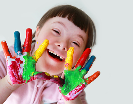 young girl with Down syndrome with paint covered palms